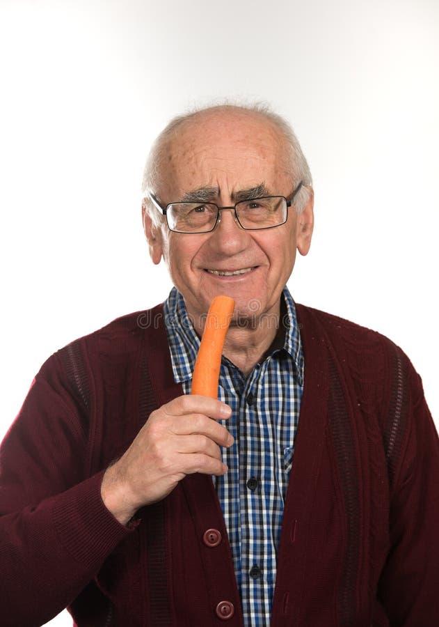 Старик есть морковь стоковое фото