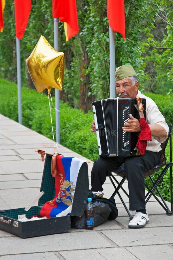 Старик играя аккордеон и пробуя заработать деньги на всю жизнь в дне победы в Волгограде стоковое изображение rf