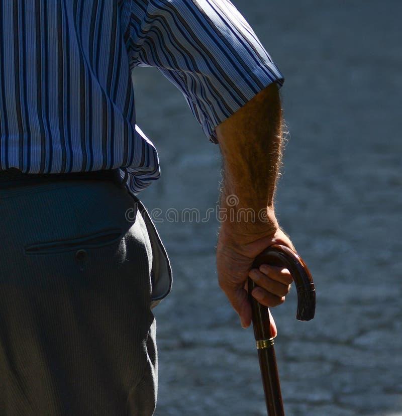 Старик идя с его руками на деревянной идя ручке стоковое фото