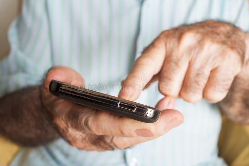 Старик используя smartphone стоковая фотография