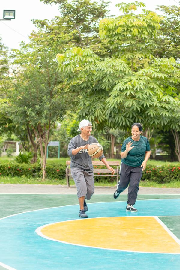 Старик и женщина для игры баскетбола в утре настолько счастливой стоковая фотография