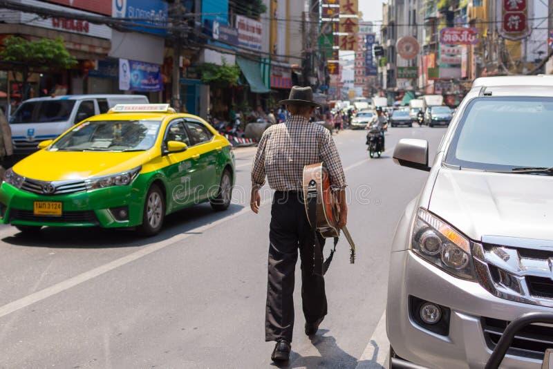 Старик идя на улицу держа гитару стоковая фотография rf