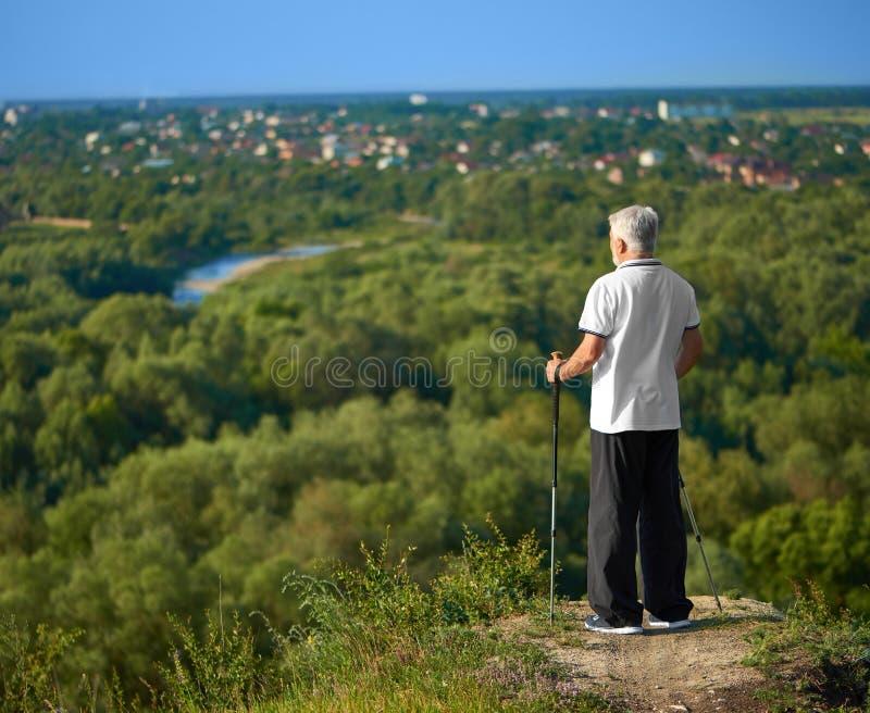 Старик наблюдая, как panorame города сдержало отслеживать вставляет стоковая фотография