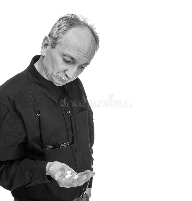 Старик принимает пилюльку стоковое изображение