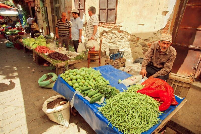 Старик продает травы, фасоли и груши на деревенском уличном рынке в Турции стоковые изображения