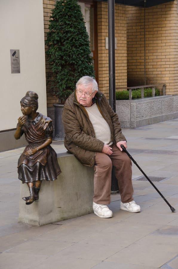 Старик рядом с статуей девушки сидя на плинтусе стоковое изображение