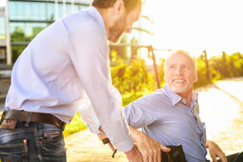 Старик сидит в кресло-коляске в парке За им стойки его сын Старик смотрит счастливо на его сыне стоковые фотографии rf