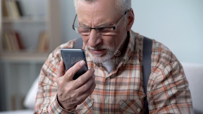 Старик смотрит недоверчиво на мобильном телефоне, новой технологии осложненной для пожилых людей стоковое изображение rf