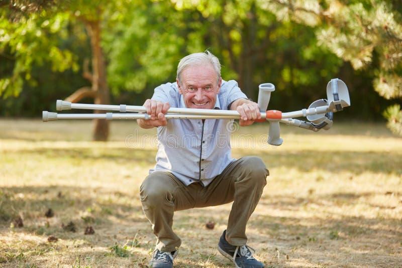 Старик с витальностью и костылями стоковое фото