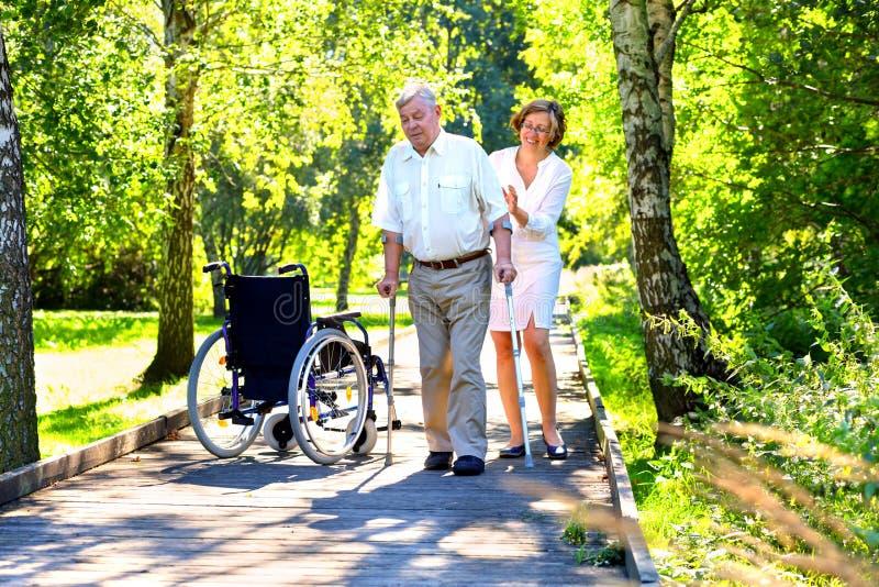 Старик с костылями и молодой женщиной в парке стоковые фото