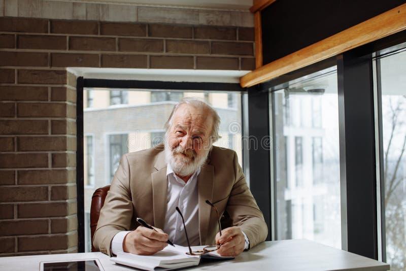 Старик с серыми волосами и борода работая с восторгом несмотря на его время стоковое фото