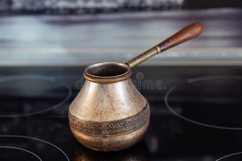Старое бронзовое турецкое ретро kanaka кофеварки на стеклянных hob и плите с деревянной ручкой, несенной на черной предпосылке в  стоковая фотография rf