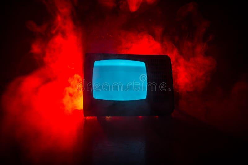 Старое винтажное красное ТВ с белым шумом на темной тонизированной туманной предпосылке Ретро старый приемник телевидения отсутст стоковые фотографии rf