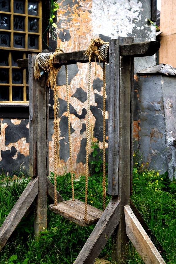 Старое деревянное качание на веревочках стоковая фотография rf