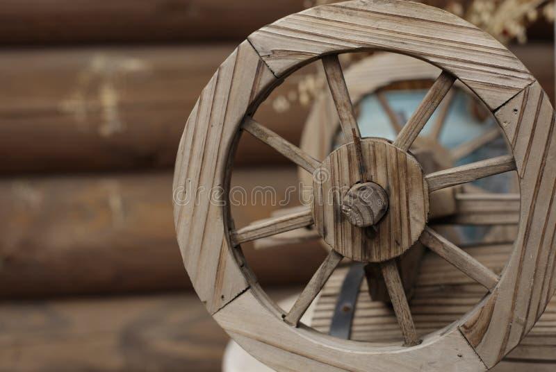 Старое деревянное колесо на предпосылке старого дома журнала стоковое фото