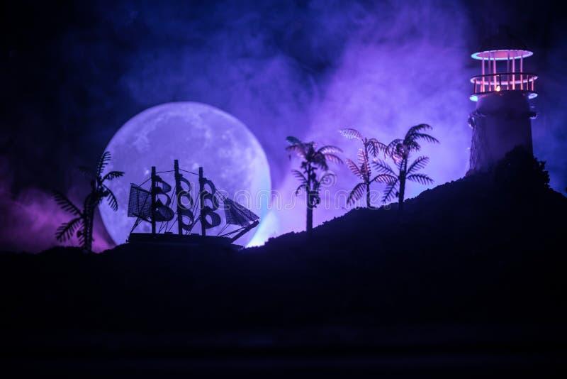Старое деревянное плавание военного корабля к ноча близко к маяку или маяку и паруснику Темная туманная предпосылка Селективный ф стоковое фото rf