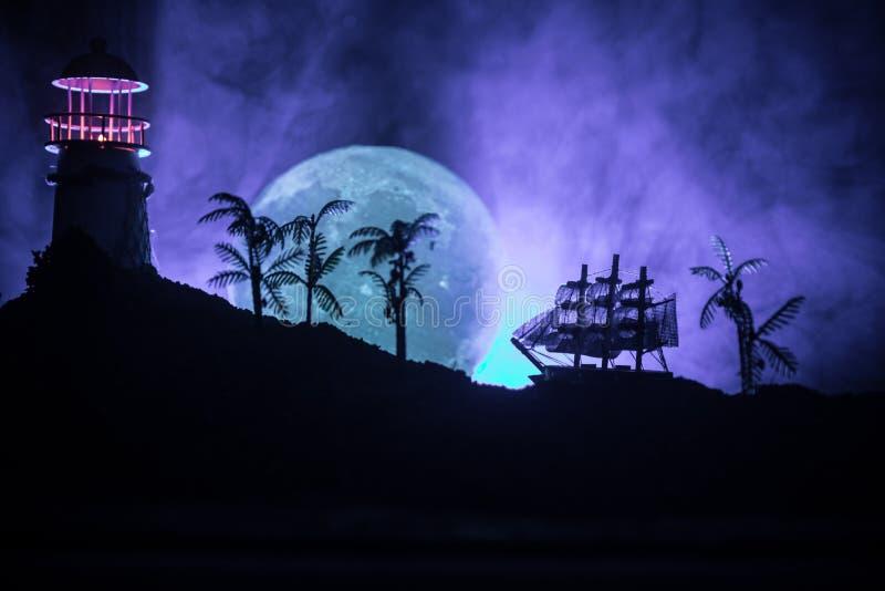 Старое деревянное плавание военного корабля к ноча близко к маяку или маяку и паруснику Темная туманная предпосылка Селективный ф стоковое изображение rf