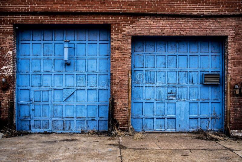 Старое деревянное яркое голубое кирпичное здание Abaondoned дверей гаража стоковые изображения