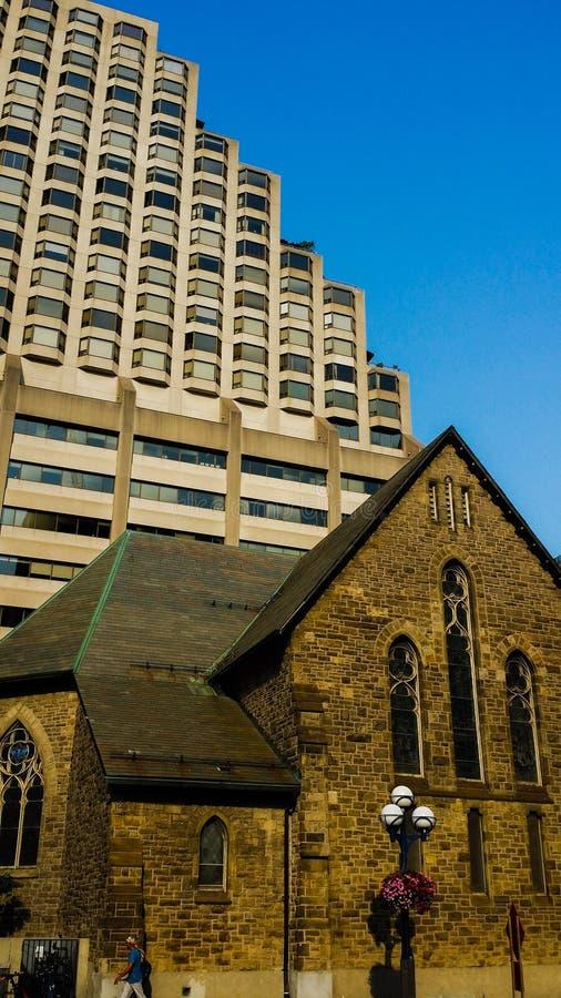 Старое здание церкви окруженное новыми зданиями highrise в Торонто стоковые изображения rf