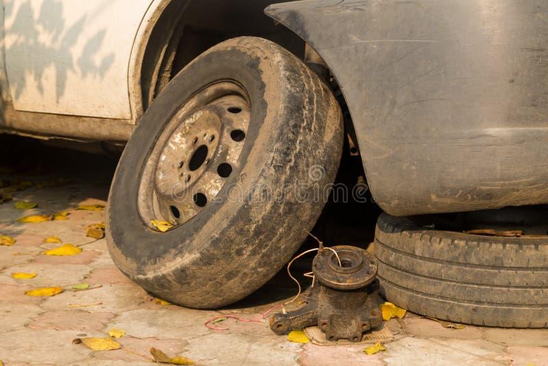 Старое колесо около белого автомобиля для ремонта стоковое изображение rf