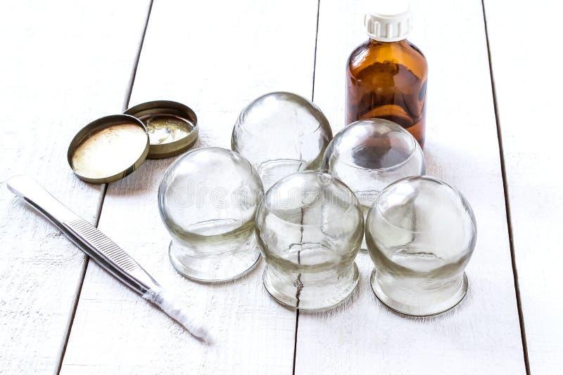 Старое медицинское придавая форму чашки стекло, спирт, петролатум и щипчики стоковое изображение rf