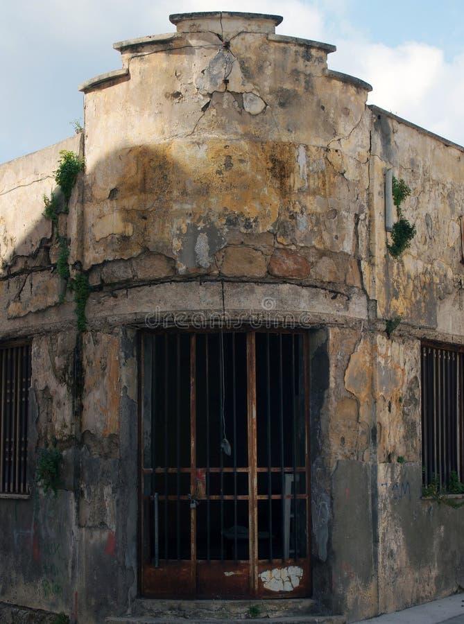 Старое покинутое покинутое комерческое имущество с крошить треснутые затрапезные стены и ржавея стальные пруты через дверь и окна стоковые фотографии rf