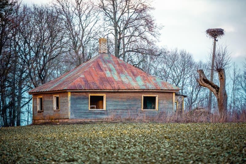 Старое получившееся отказ деревянное гнездо дома и аиста на куче около ее стоковое изображение rf