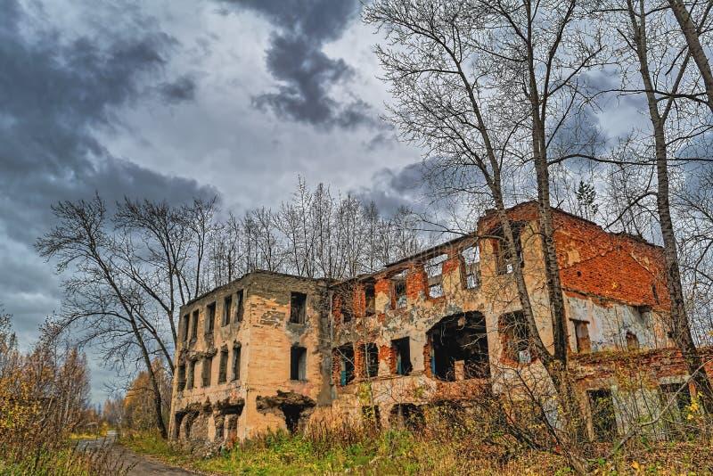 Старое получившееся отказ кирпичное здание на предпосылке дождливого неба осени стоковые фотографии rf
