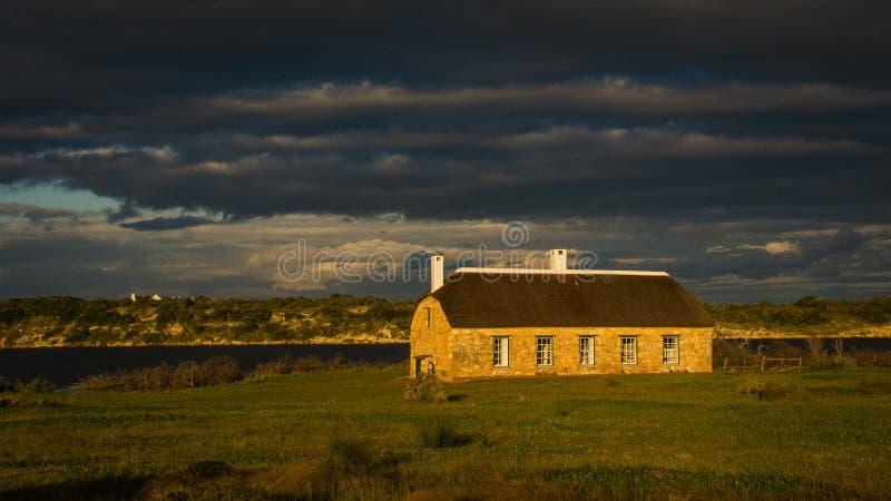 Старое сельскохозяйственное строительство загорено заходящим солнцем под glowering бурным небом стоковое изображение