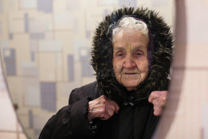 Старое счастливое отражение женщины в outerwear зимы зеркала нося стоковое изображение rf