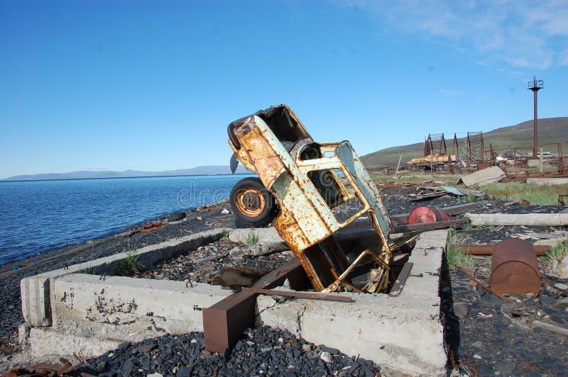 Старое сломанное ржавое покинутое побережье автомобиля вверх ногами на море стоковое фото rf