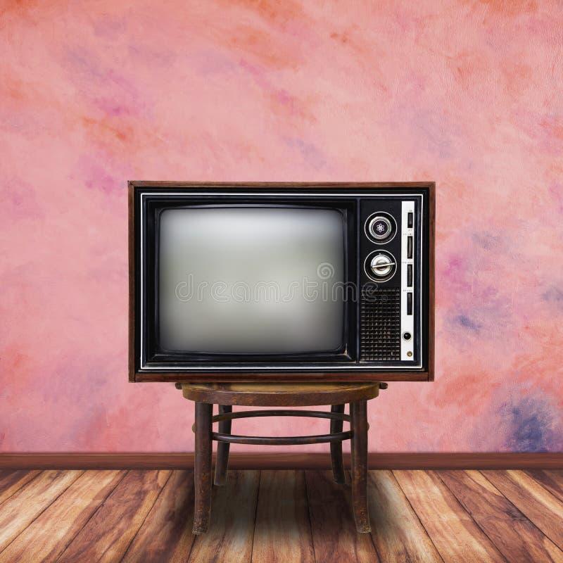Старое телевидение на деревянном стуле в предпосылке комнаты стоковые фото