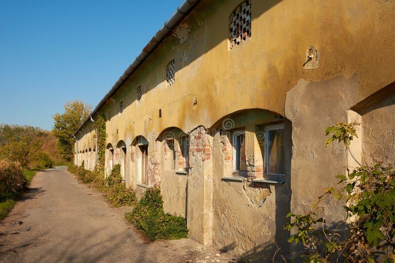 Старое треснутое здание - казармы или сельский дом, дорога асфальта в th стоковая фотография rf
