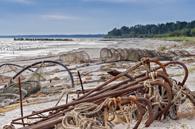 Старое удя оборудование и сломленная пристань на прибалтийском пляже стоковое изображение rf