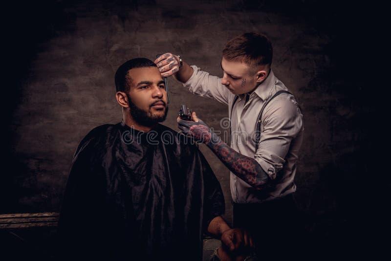 Старомодным парикмахер татуированный профессионалом делает стрижку к Афро-американскому клиенту на текстурированной темноте стоковая фотография rf
