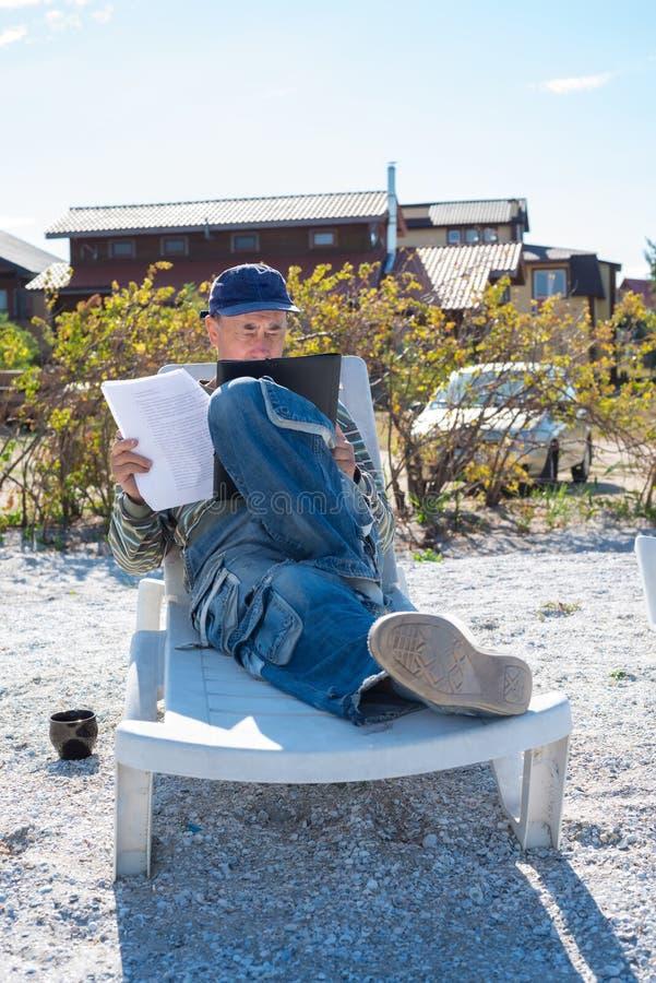 Старомодный бизнесмен сидит в deckchair морем стоковые изображения rf
