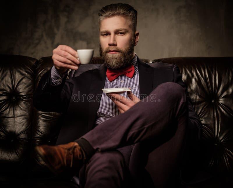Старомодный бородатый человек сидя в удобной кожаной софе с чашкой кофе на сером цвете стоковые фотографии rf