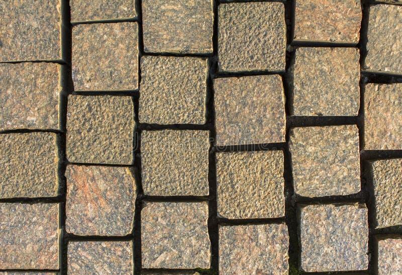 Старо-серый красный гранит разрушил каменную тротуарку из каменных кирпичей текстура грубой поверхности стоковое фото