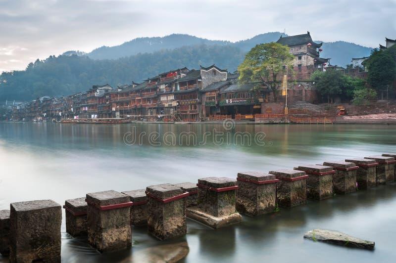 Стартовые площадки через реку Tuojiang с северным стробом возвышаются на заднем плане в Fenghuang, провинции Хунань, Китае стоковое изображение
