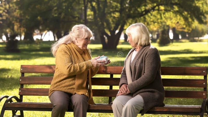 Старуха давая подарок на день рождения другу на стенде в парке, золотые леты стоковое изображение rf