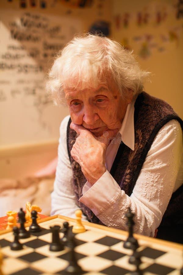 Старуха играет шахматы t стоковые фото