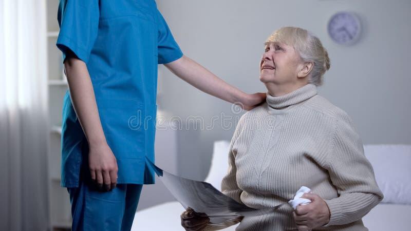 Старуха медсестры поддерживая плача с рентгеном мозга, смертоносным диагнозом, здоровьем стоковые фотографии rf