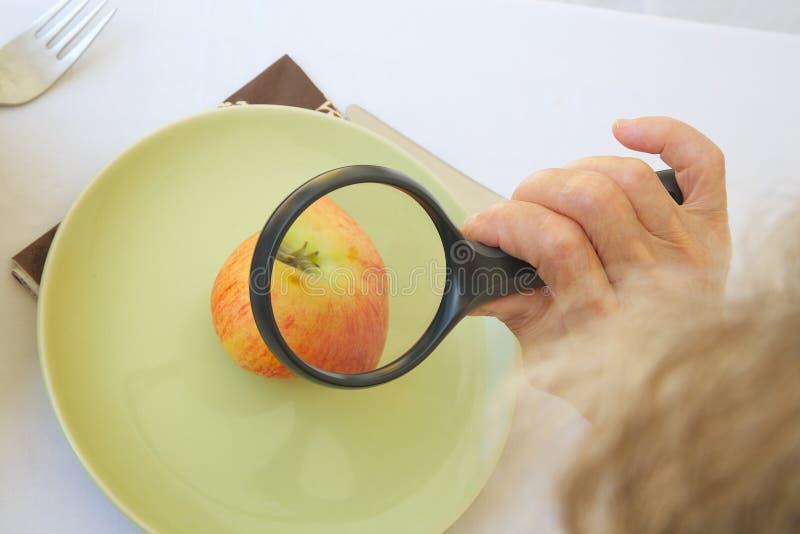 Старуха наблюдает яблоком под лупой стоковое фото rf