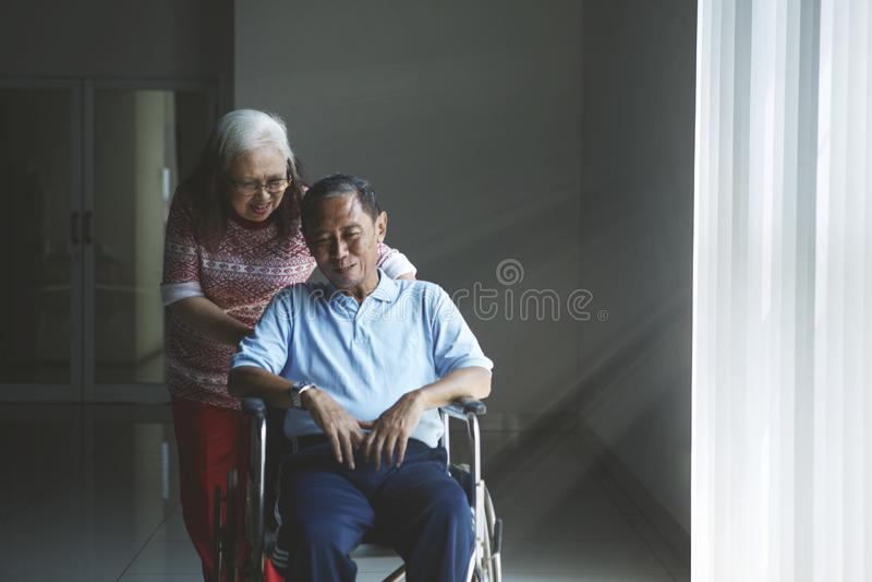 Старуха нажимает ее супруга в кресло-коляске стоковая фотография