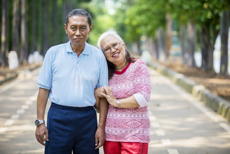 Старуха обнимая ее супруга на дороге стоковые фотографии rf