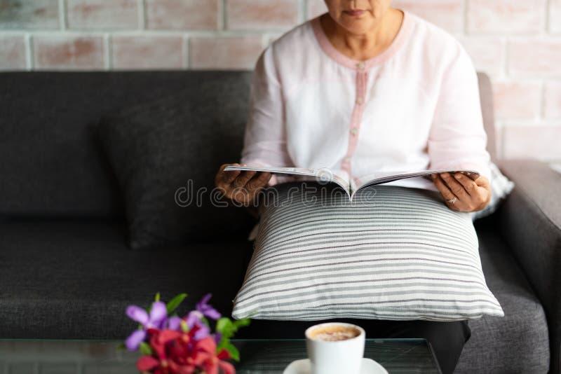 Старуха читая книгу с чашкой кофе дома стоковые фото