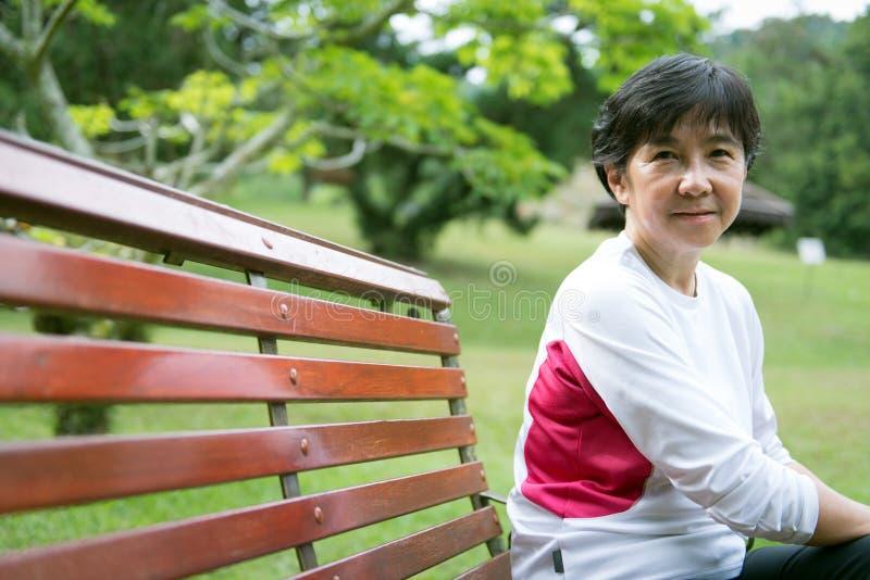 Старшая азиатская женщина в парке стоковое изображение