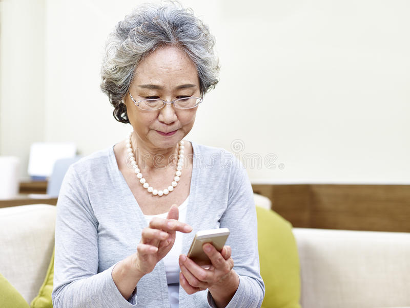 Старшая азиатская женщина используя мобильный телефон стоковая фотография rf