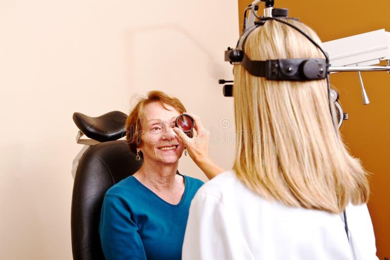 Старшая дама имея проверку глаза вверх стоковое изображение