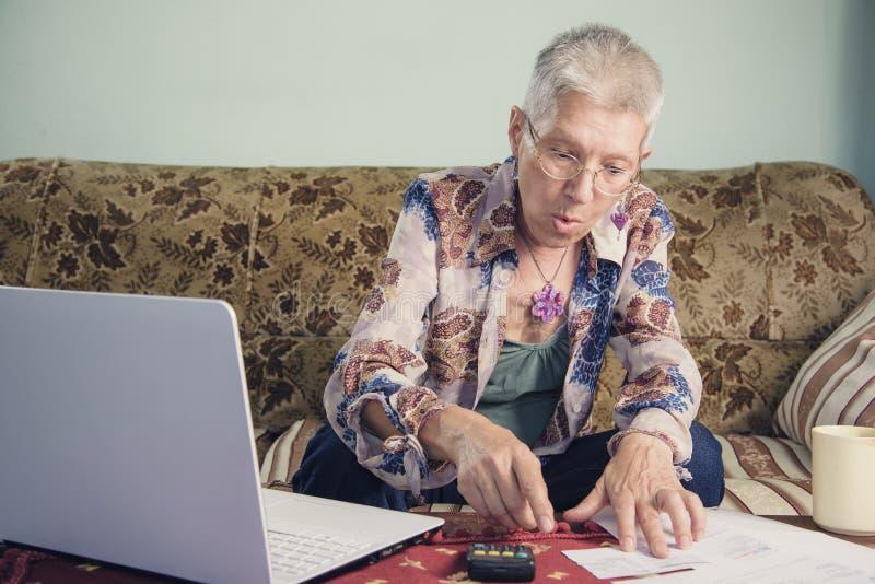 Старшая дама сотрясенная с ее счетами стоковое изображение